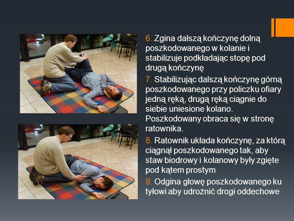 6. Zgina dalszą kończynę dolną poszkodowanego w kolanie i stabilizuje podkładając stopę pod drugą kończynę