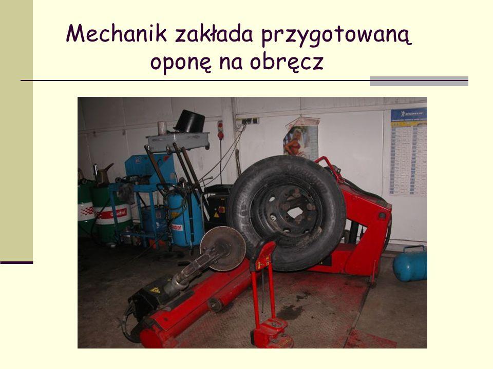 Mechanik zakłada przygotowaną oponę na obręcz