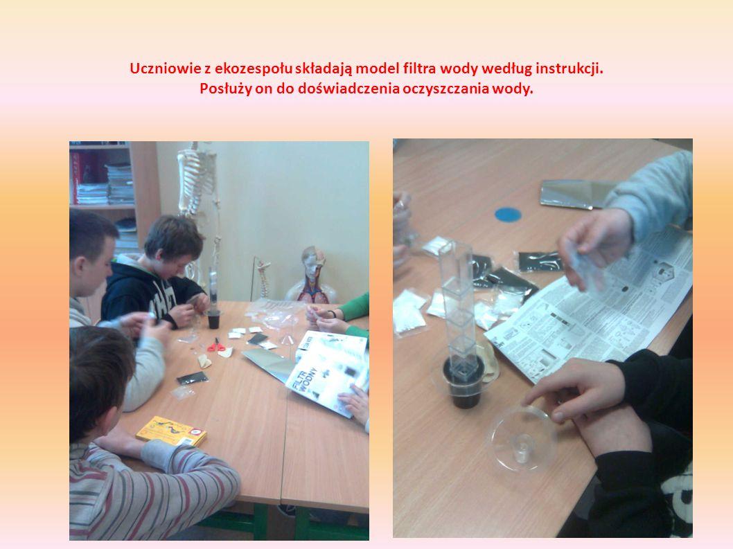 Uczniowie z ekozespołu składają model filtra wody według instrukcji