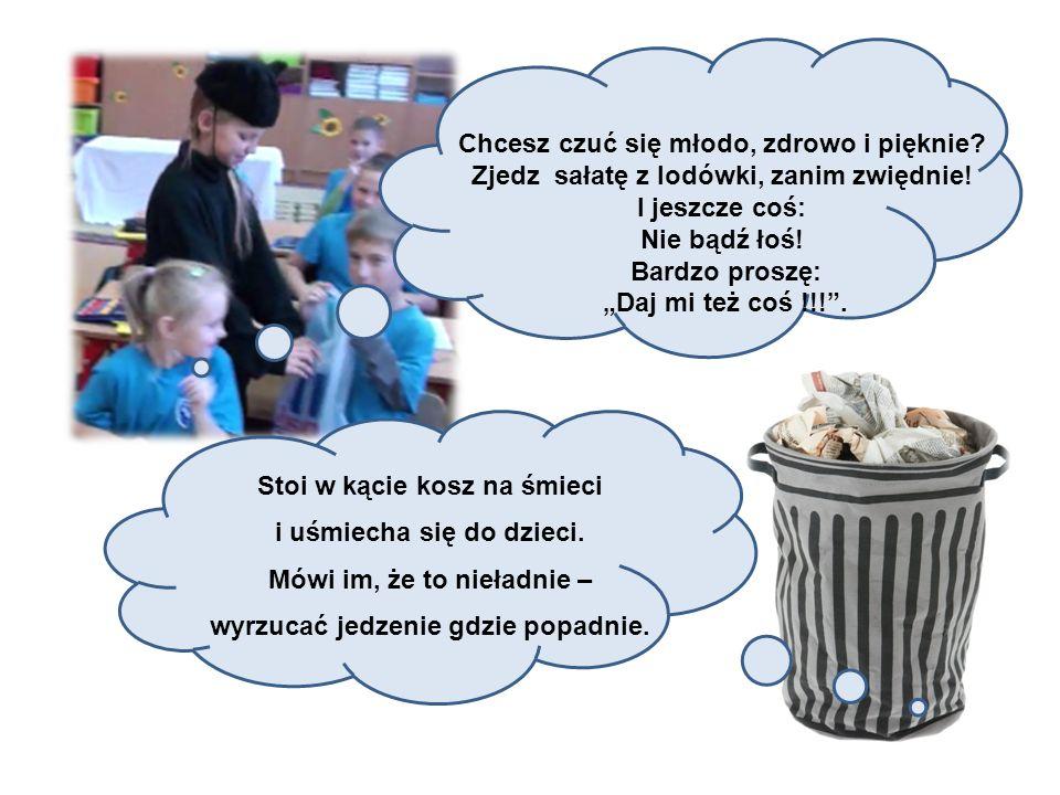 Stoi w kącie kosz na śmieci i uśmiecha się do dzieci.