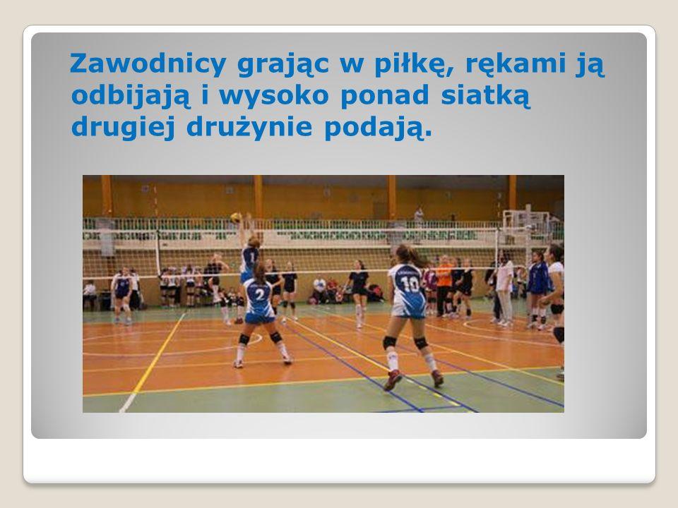 Zawodnicy grając w piłkę, rękami ją odbijają i wysoko ponad siatką drugiej drużynie podają.