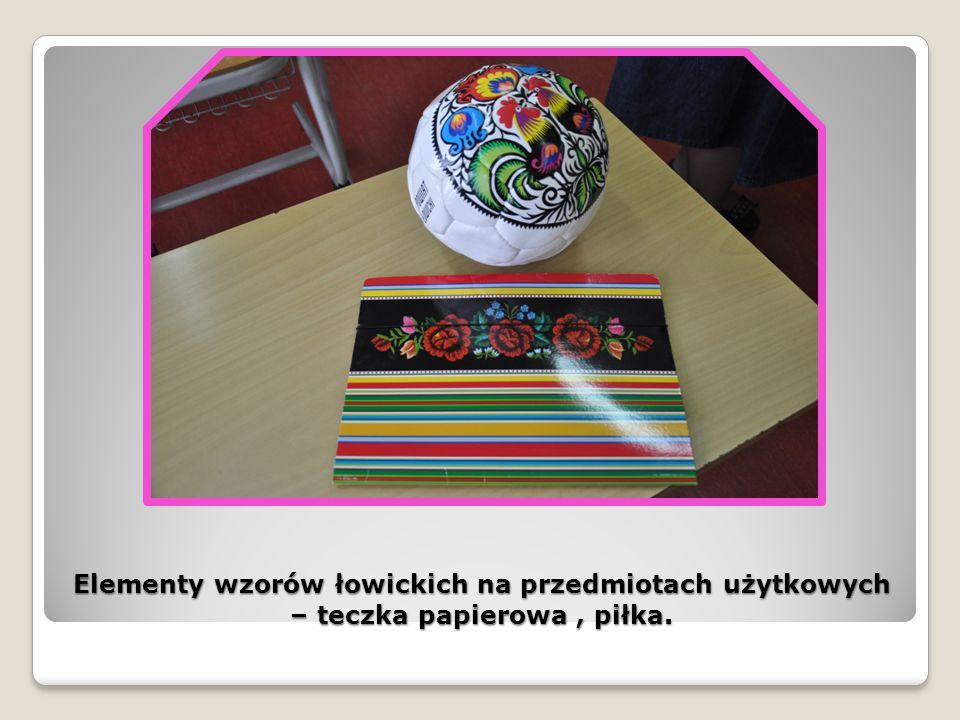 Elementy wzorów łowickich na przedmiotach użytkowych – teczka papierowa , piłka.