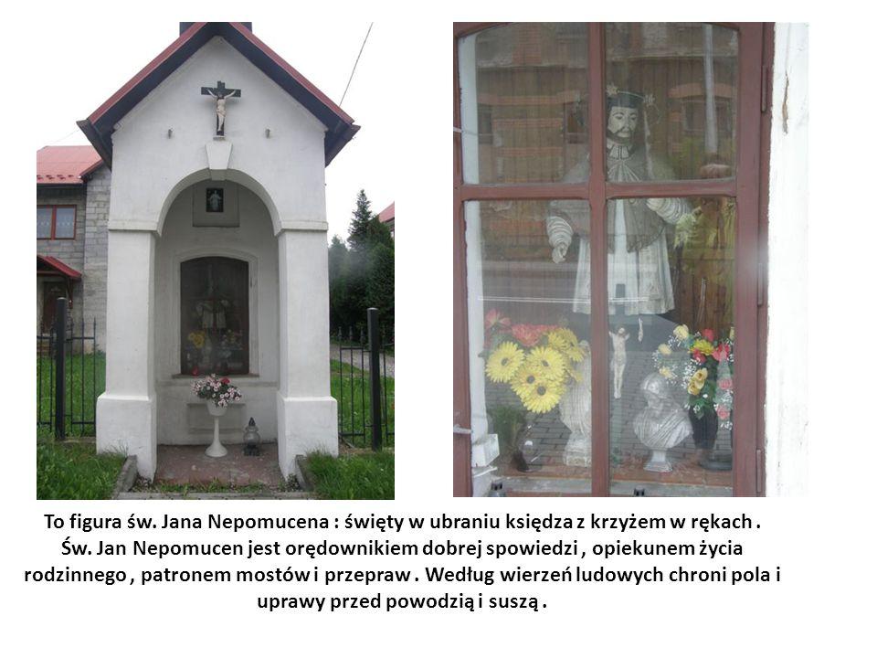 To figura św. Jana Nepomucena : święty w ubraniu księdza z krzyżem w rękach .