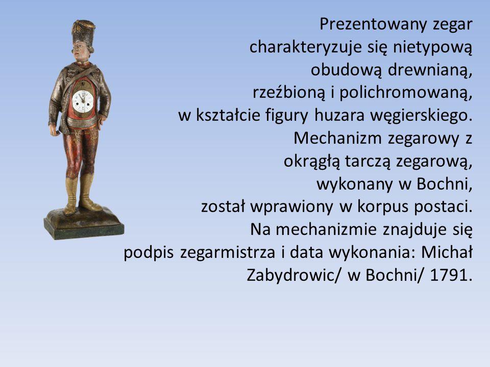 Prezentowany zegar charakteryzuje się nietypową obudową drewnianą, rzeźbioną i polichromowaną, w kształcie figury huzara węgierskiego.