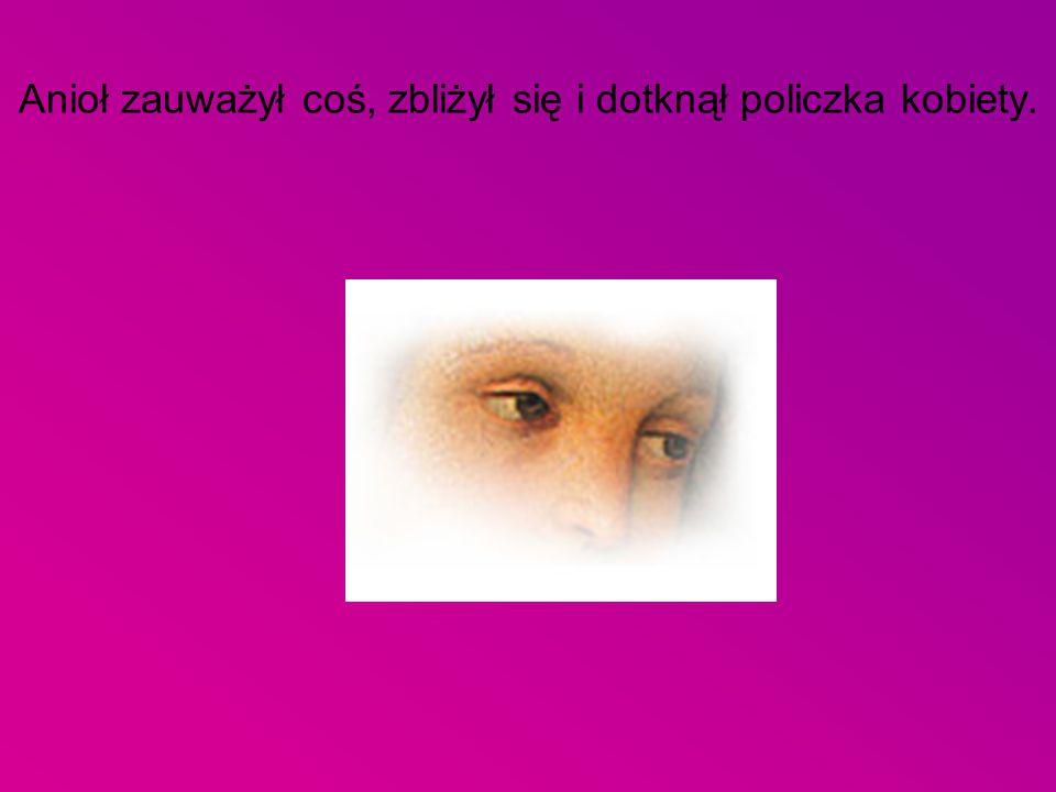 Anioł zauważył coś, zbliżył się i dotknął policzka kobiety.