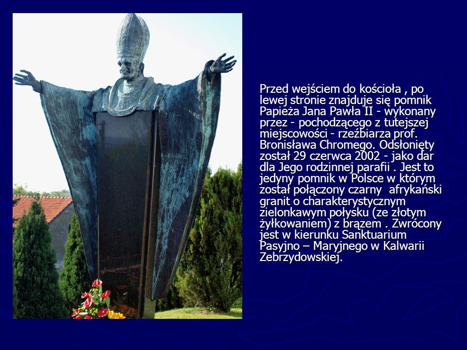 Przed wejściem do kościoła , po lewej stronie znajduje się pomnik Papieża Jana Pawła II - wykonany przez - pochodzącego z tutejszej miejscowości - rzeźbiarza prof.
