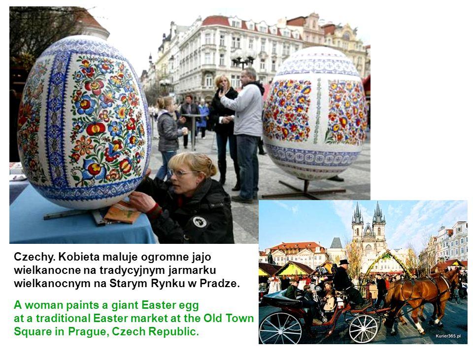 Czechy. Kobieta maluje ogromne jajo wielkanocne na tradycyjnym jarmarku wielkanocnym na Starym Rynku w Pradze.