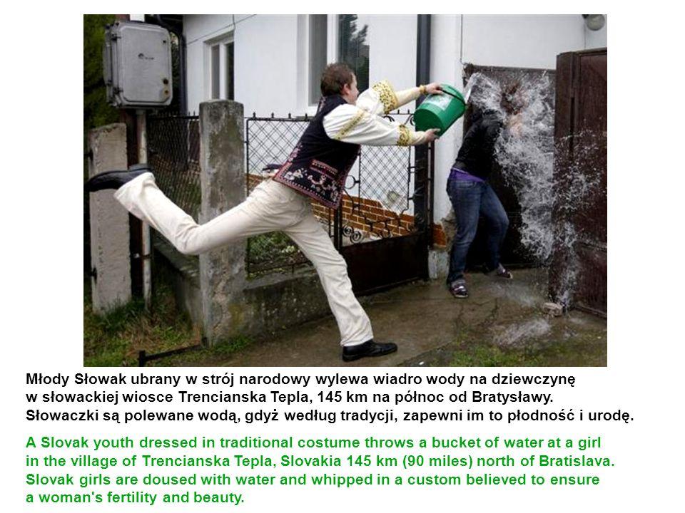 Młody Słowak ubrany w strój narodowy wylewa wiadro wody na dziewczynę