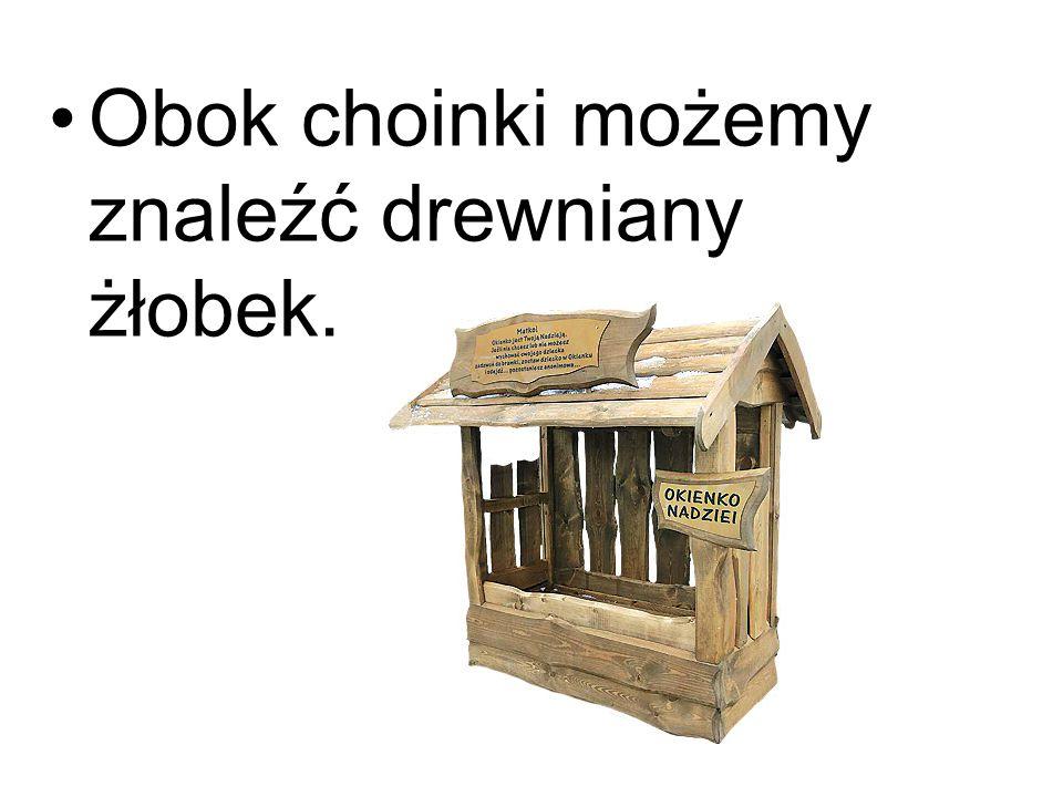 Obok choinki możemy znaleźć drewniany żłobek.