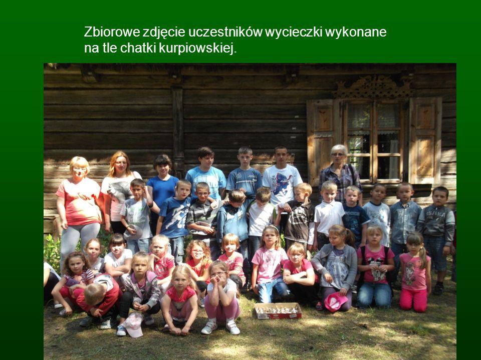 Zbiorowe zdjęcie uczestników wycieczki wykonane na tle chatki kurpiowskiej.