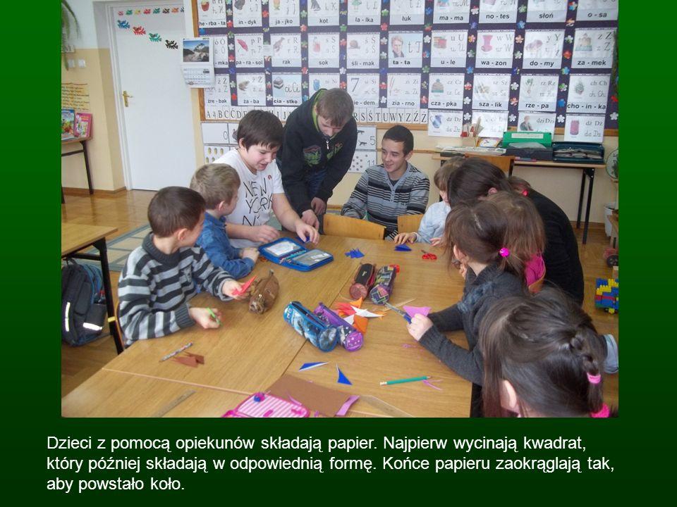Dzieci z pomocą opiekunów składają papier
