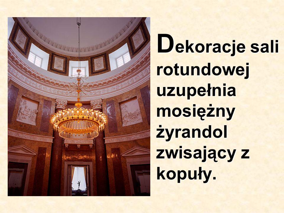 Dekoracje sali rotundowej uzupełnia mosiężny żyrandol zwisający z kopuły.