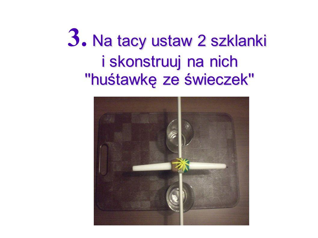3. Na tacy ustaw 2 szklanki i skonstruuj na nich huśtawkę ze świeczek