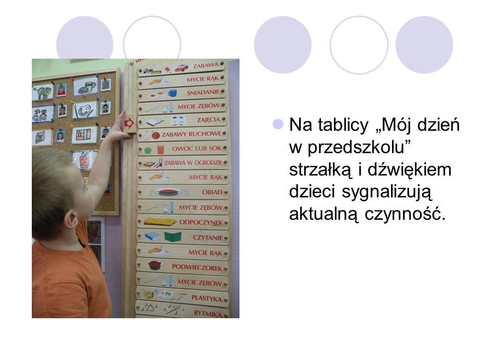 """Na tablicy """"Mój dzień w przedszkolu strzałką i dźwiękiem dzieci sygnalizują aktualną czynność."""