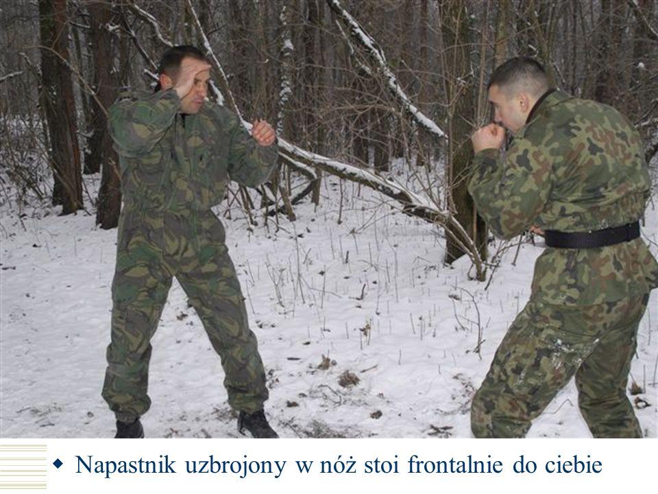 Napastnik uzbrojony w nóż stoi frontalnie do ciebie