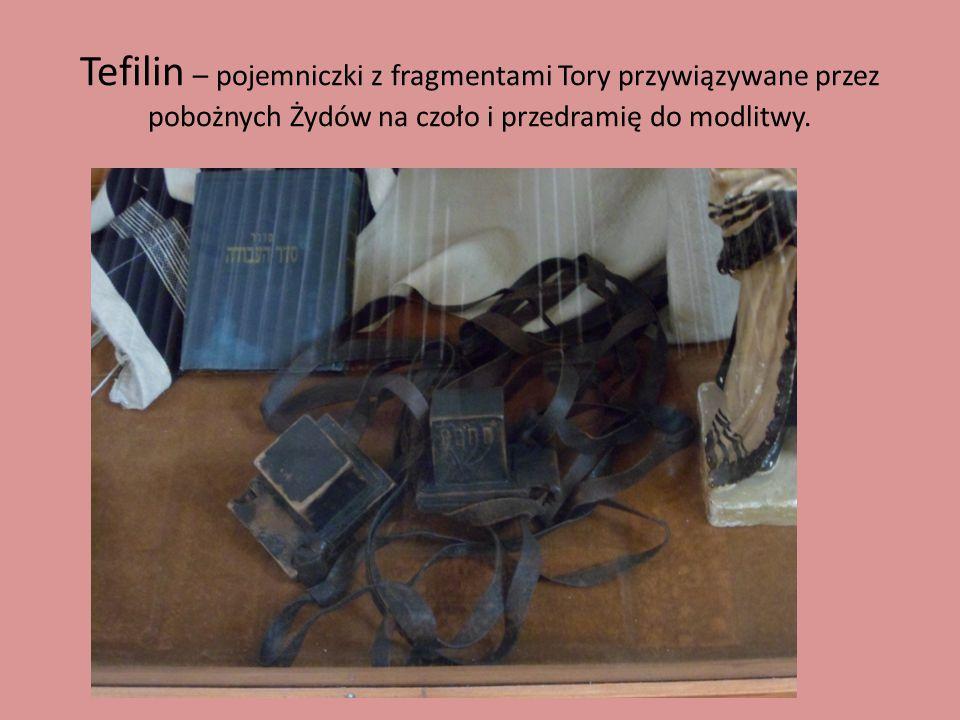 Tefilin – pojemniczki z fragmentami Tory przywiązywane przez pobożnych Żydów na czoło i przedramię do modlitwy.