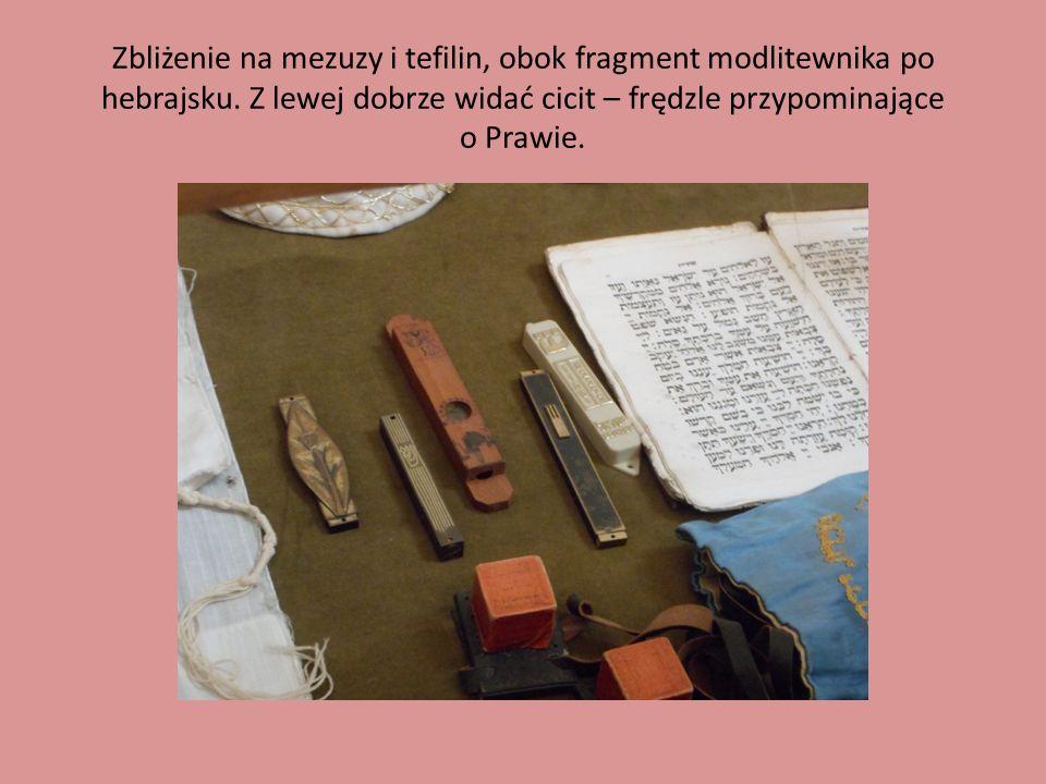 Zbliżenie na mezuzy i tefilin, obok fragment modlitewnika po hebrajsku