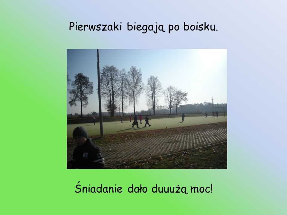 Pierwszaki biegają po boisku.