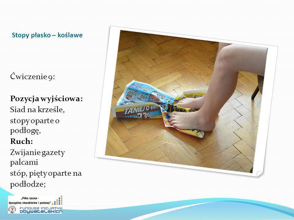 Zwijanie gazety palcami stóp, pięty oparte na podłodze;