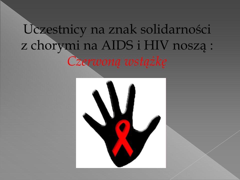 Uczestnicy na znak solidarności z chorymi na AIDS i HIV noszą : Czerwoną wstążkę