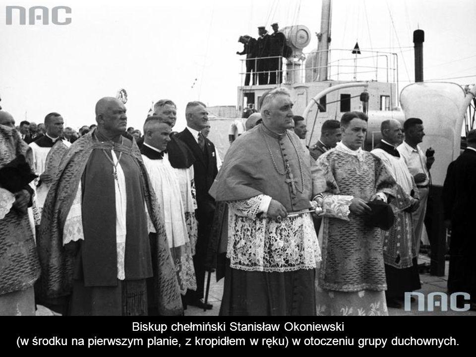 Biskup chełmiński Stanisław Okoniewski (w środku na pierwszym planie, z kropidłem w ręku) w otoczeniu grupy duchownych.