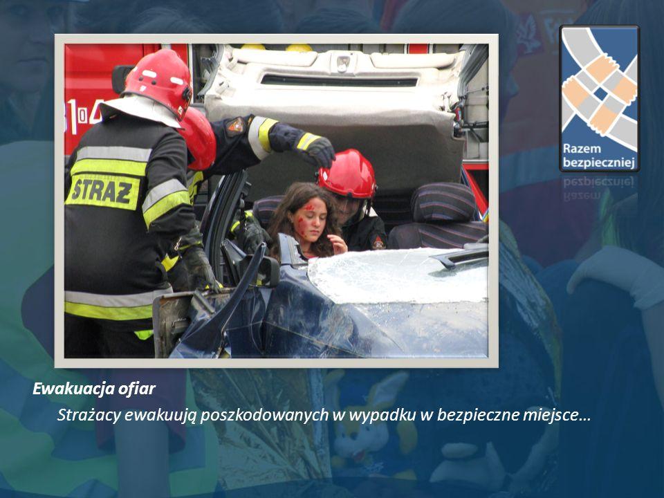 Ewakuacja ofiar Strażacy ewakuują poszkodowanych w wypadku w bezpieczne miejsce…