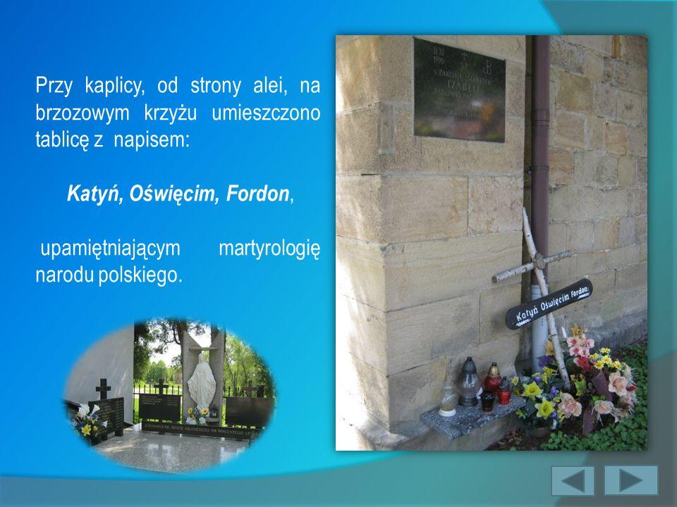 Przy kaplicy, od strony alei, na brzozowym krzyżu umieszczono tablicę z napisem: