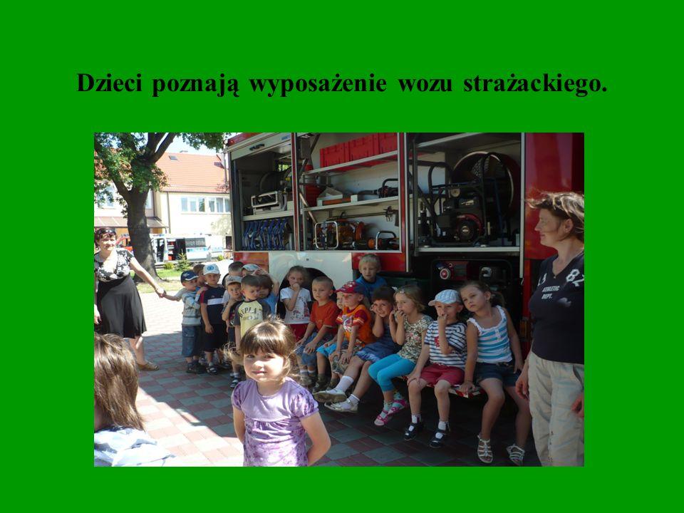 Dzieci poznają wyposażenie wozu strażackiego.