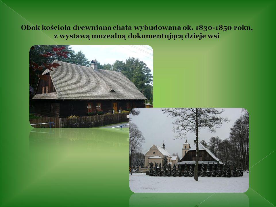 Obok kościoła drewniana chata wybudowana ok