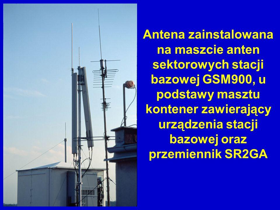 Antena zainstalowana na maszcie anten sektorowych stacji bazowej GSM900, u podstawy masztu kontener zawierający urządzenia stacji bazowej oraz przemiennik SR2GA