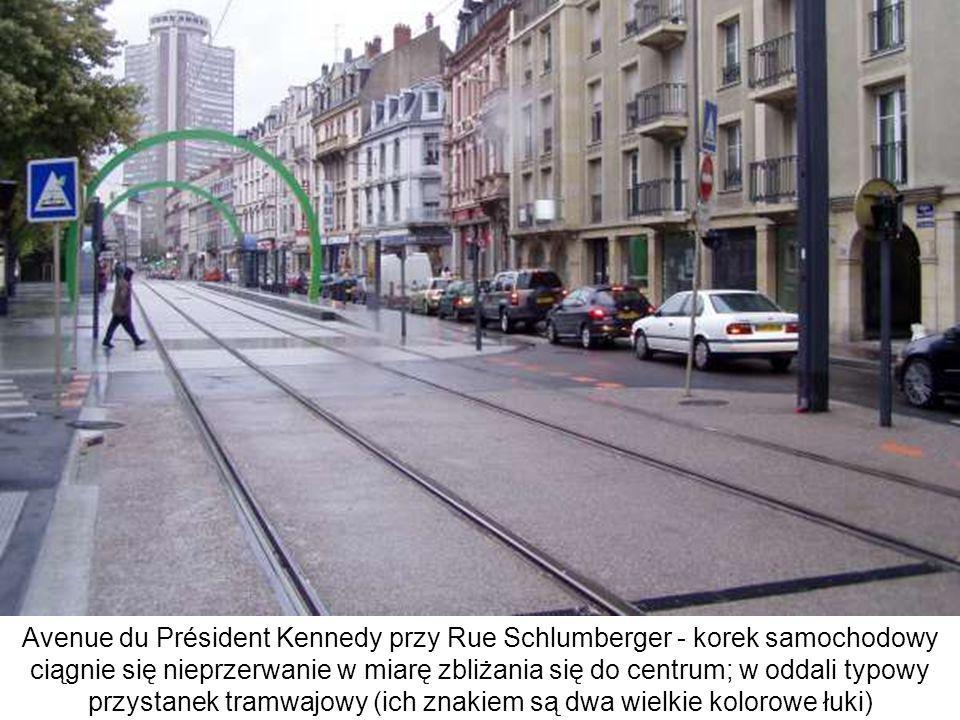Avenue du Président Kennedy przy Rue Schlumberger - korek samochodowy ciągnie się nieprzerwanie w miarę zbliżania się do centrum; w oddali typowy przystanek tramwajowy (ich znakiem są dwa wielkie kolorowe łuki)