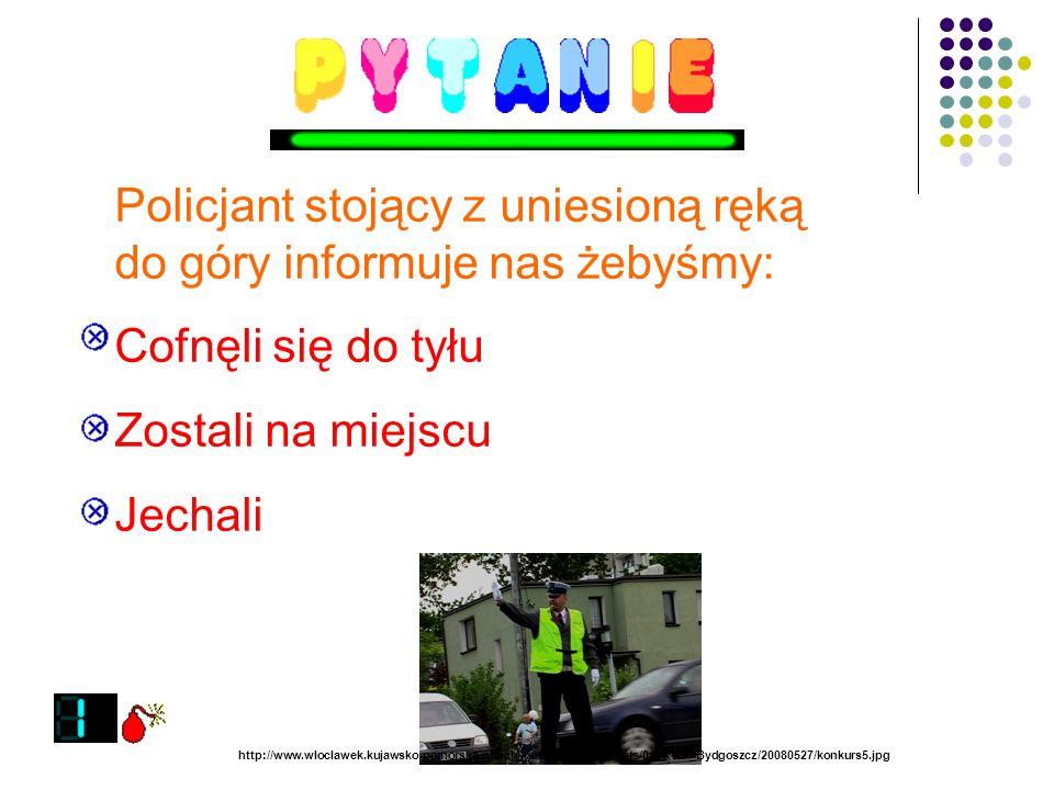 Policjant stojący z uniesioną ręką do góry informuje nas żebyśmy: