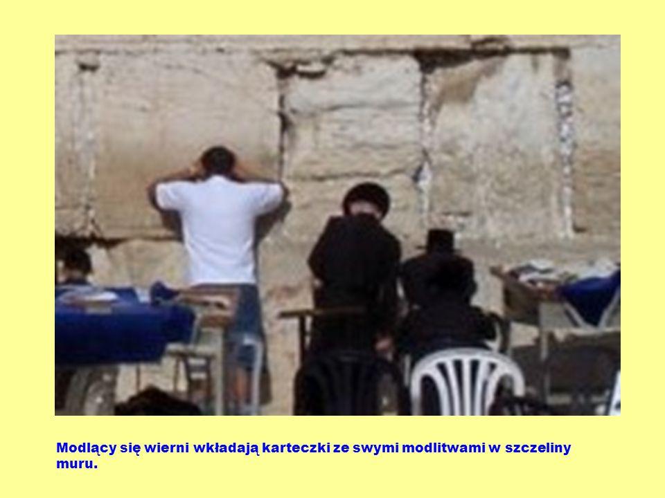 Modlący się wierni wkładają karteczki ze swymi modlitwami w szczeliny muru.