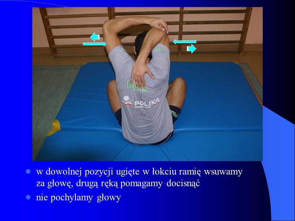 w dowolnej pozycji ugięte w łokciu ramię wsuwamy za głowę, drugą ręką pomagamy docisnąć