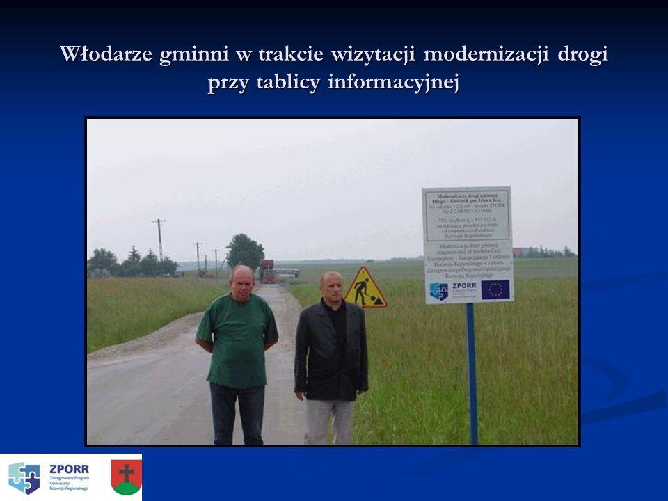 Włodarze gminni w trakcie wizytacji modernizacji drogi przy tablicy informacyjnej