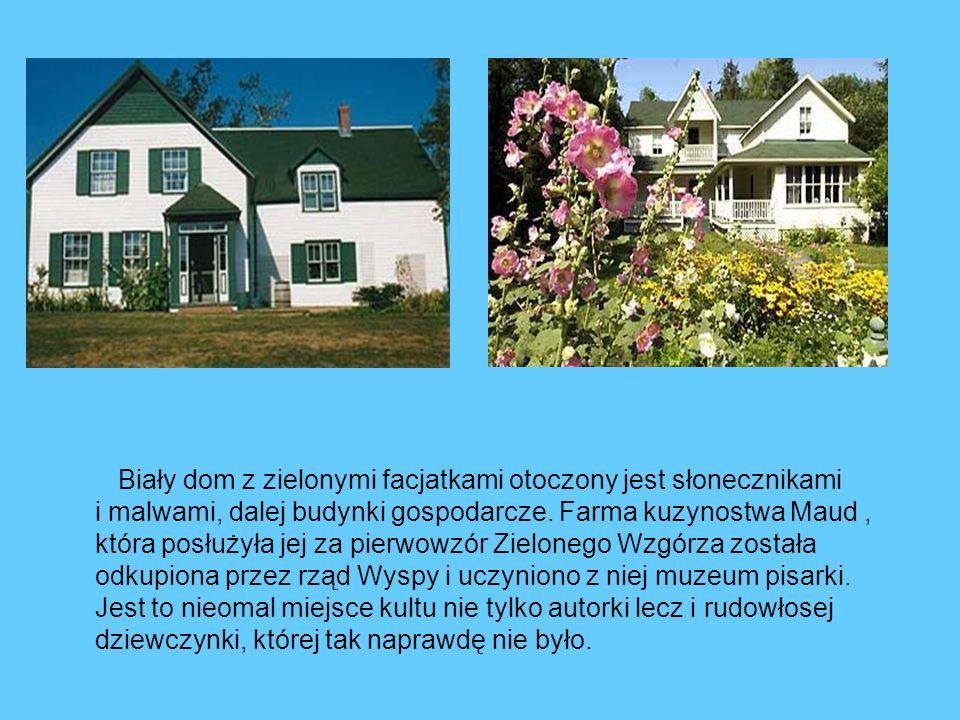 Biały dom z zielonymi facjatkami otoczony jest słonecznikami i malwami, dalej budynki gospodarcze.