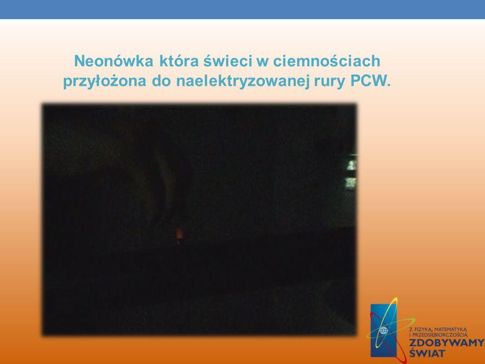 Neonówka która świeci w ciemnościach przyłożona do naelektryzowanej rury PCW.