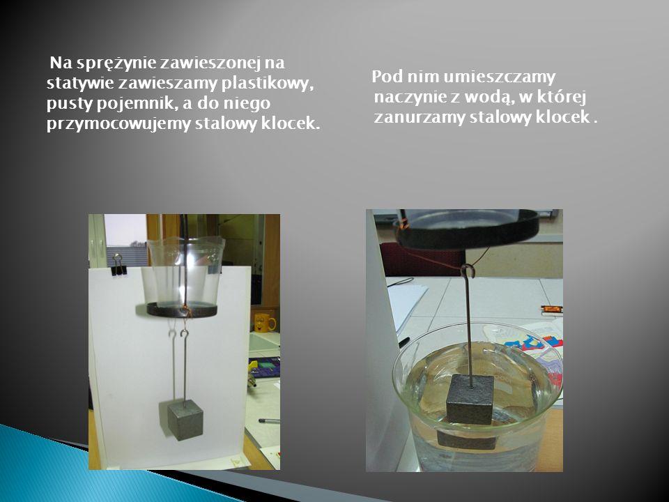 Na sprężynie zawieszonej na statywie zawieszamy plastikowy, pusty pojemnik, a do niego przymocowujemy stalowy klocek.
