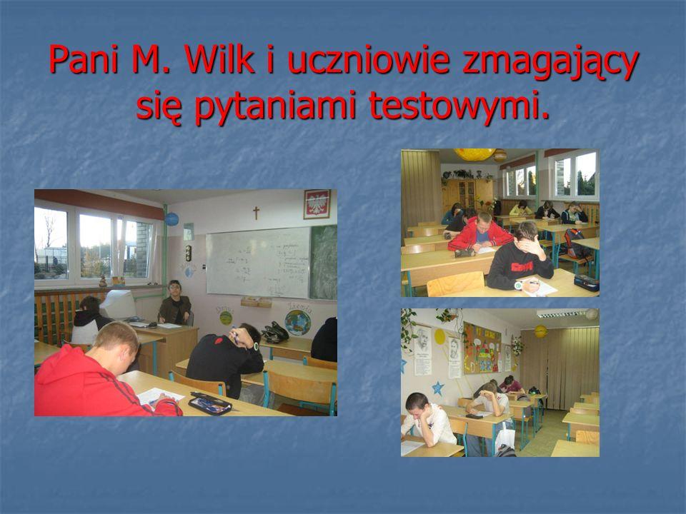 Pani M. Wilk i uczniowie zmagający się pytaniami testowymi.