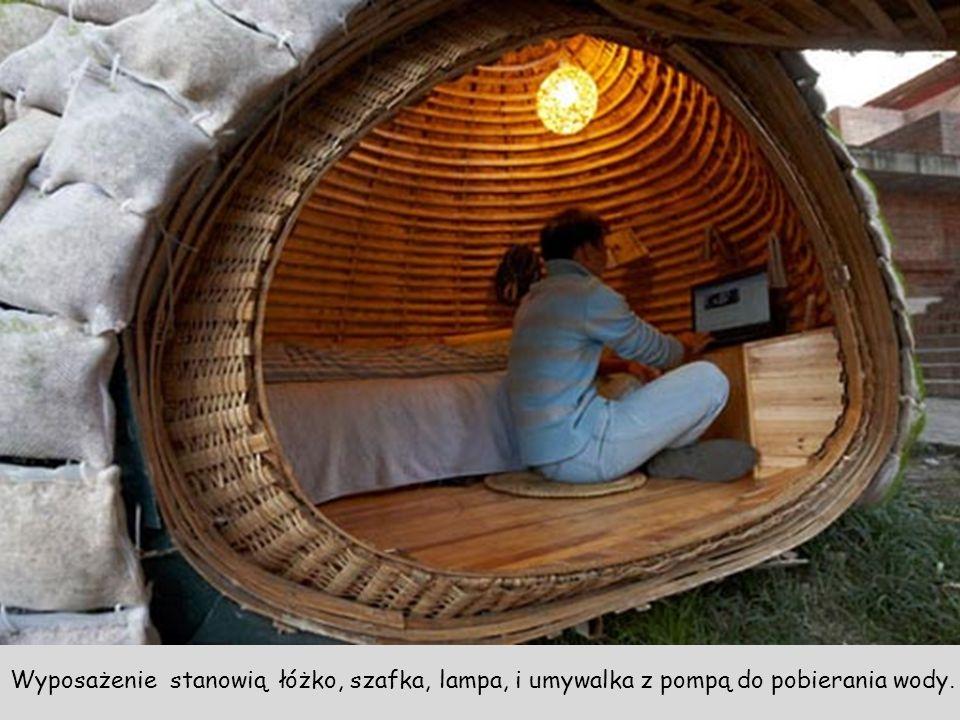 Wyposażenie stanowią łóżko, szafka, lampa, i umywalka z pompą do pobierania wody.