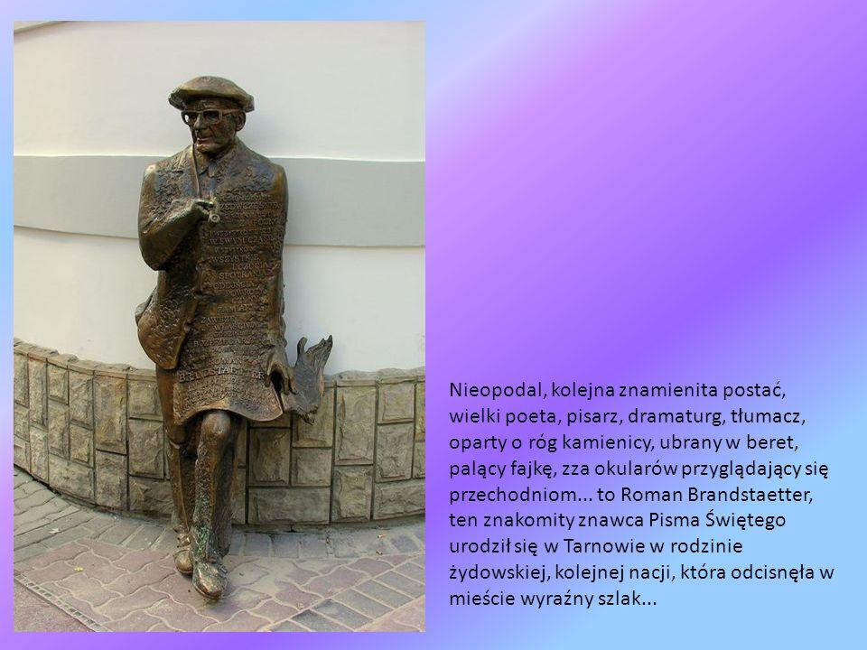 Nieopodal, kolejna znamienita postać, wielki poeta, pisarz, dramaturg, tłumacz, oparty o róg kamienicy, ubrany w beret, palący fajkę, zza okularów przyglądający się przechodniom...