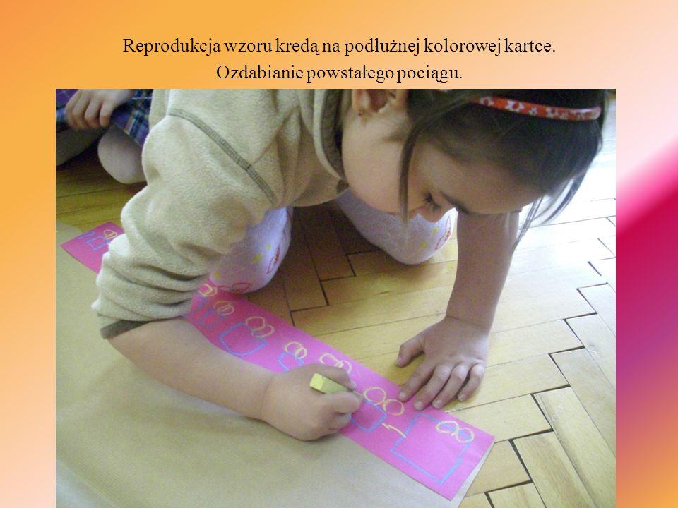 Reprodukcja wzoru kredą na podłużnej kolorowej kartce.