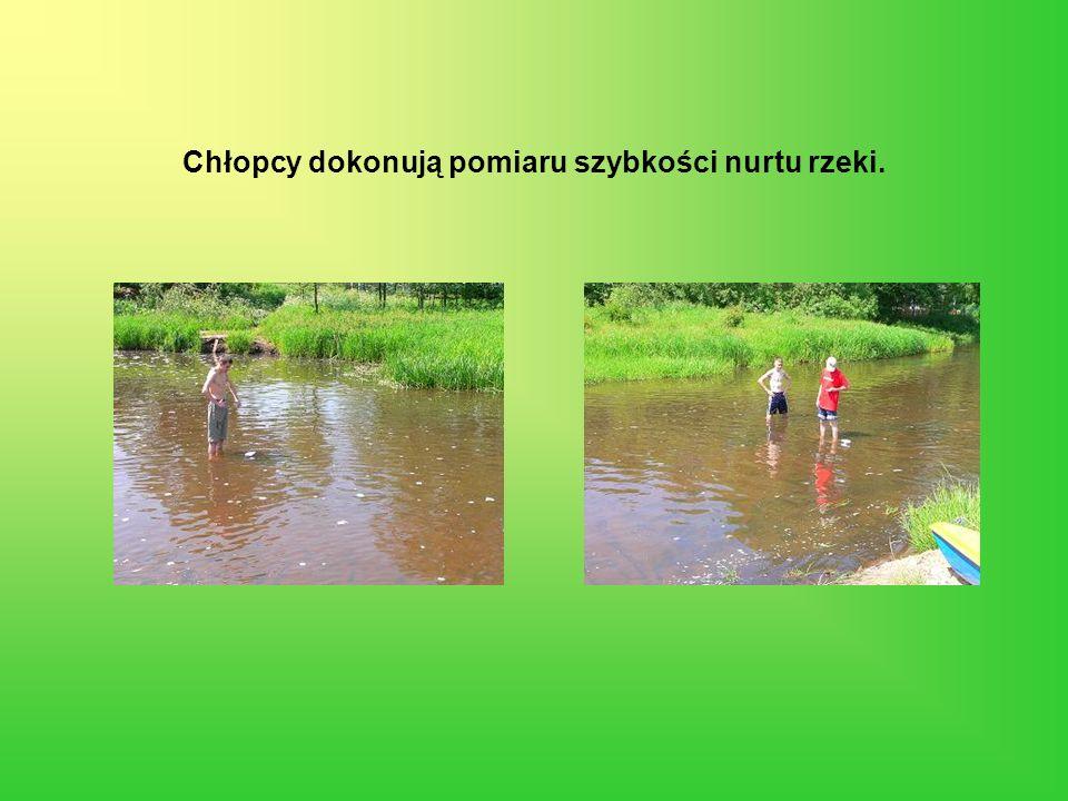 Chłopcy dokonują pomiaru szybkości nurtu rzeki.