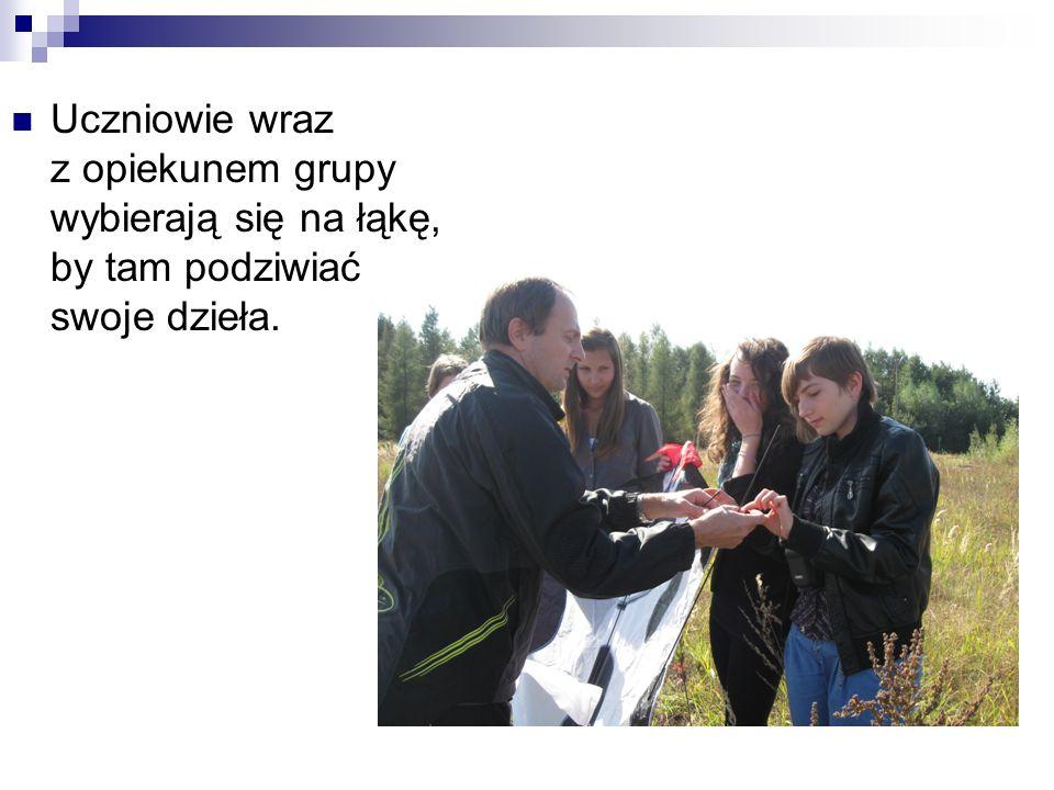 Uczniowie wraz z opiekunem grupy wybierają się na łąkę, by tam podziwiać swoje dzieła.
