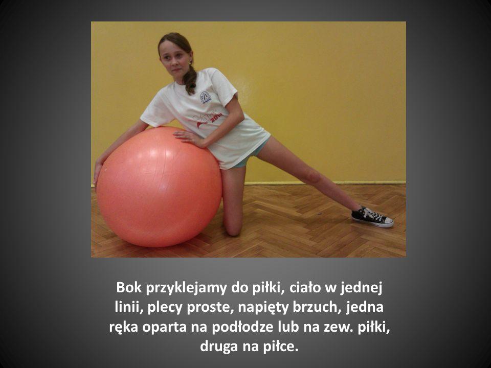 Bok przyklejamy do piłki, ciało w jednej linii, plecy proste, napięty brzuch, jedna ręka oparta na podłodze lub na zew.