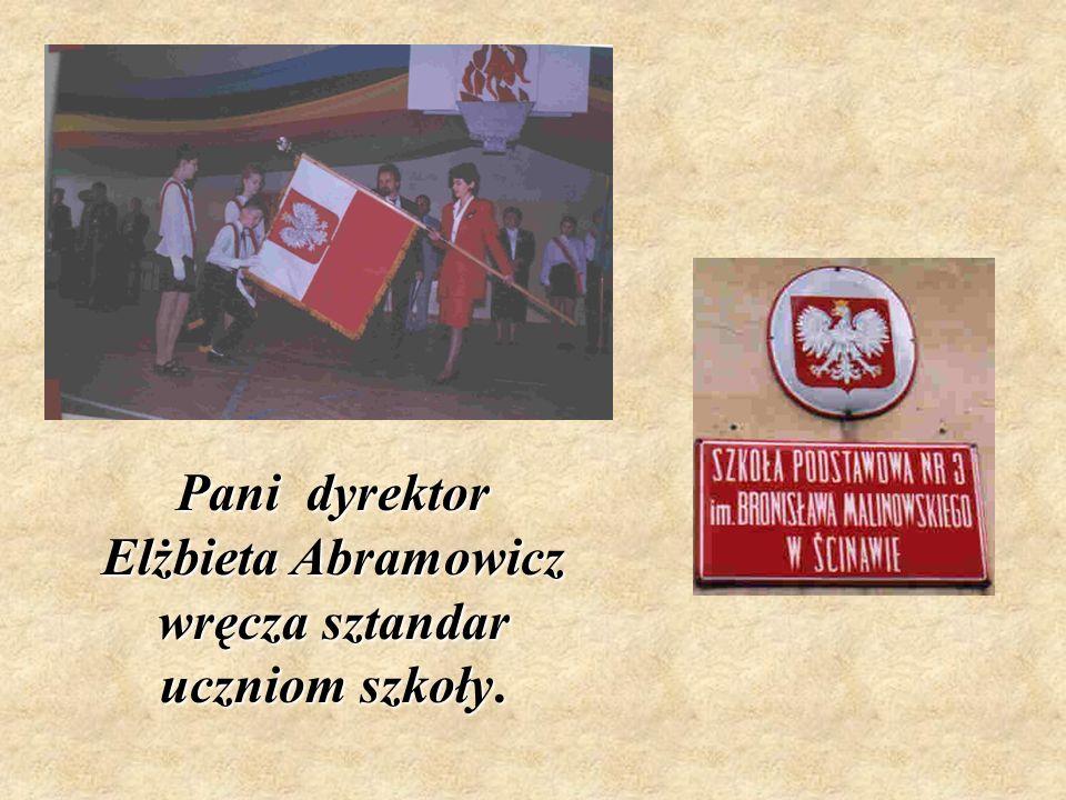 Pani dyrektor Elżbieta Abramowicz wręcza sztandar uczniom szkoły.