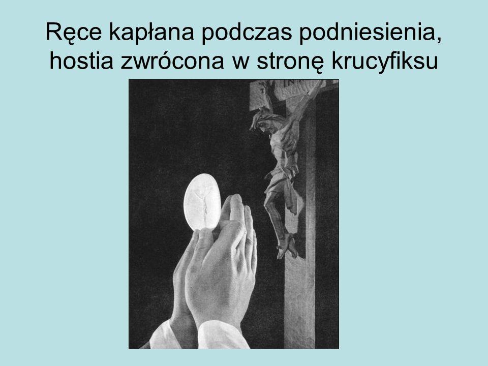 Ręce kapłana podczas podniesienia, hostia zwrócona w stronę krucyfiksu